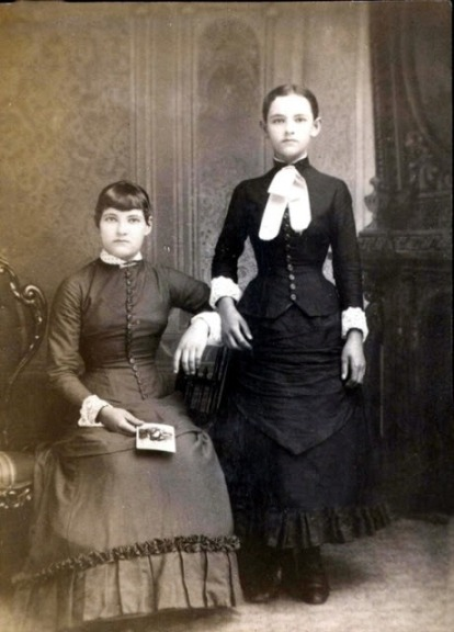 It was common in the Victorian era to photograph the dead as a keepsake. The girl standing is deceased, she is propped up with a stand.